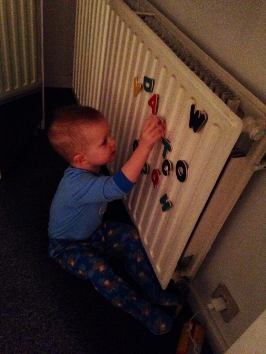 Playing in the hotel room after a long day of sight-seeing, and excited to discover that his letter magnets stick to the radiator!  (Don't worry, the radiator isn't on...)